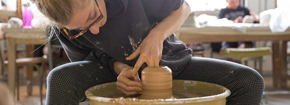 Open University student learning to throw pots in art classroom