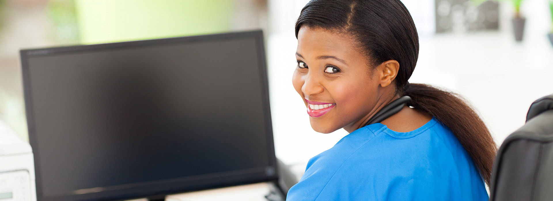 Clinical Medical Assistant (CMA) smiling while using the computer