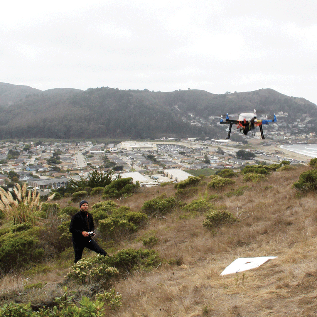 Student flying a drone on a hill