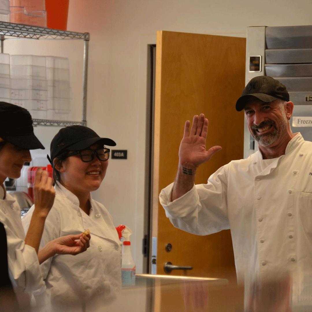 Chef and student kitchen staff wave