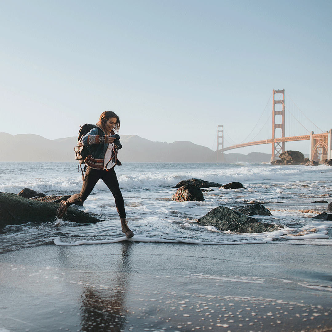 International student on a beach, with the Golden Gate Bridge in the background