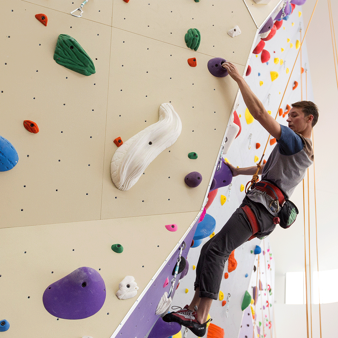 Student rock climbing at the campus gym